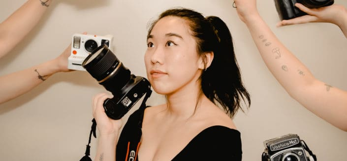 Woman holding a camera while looking up